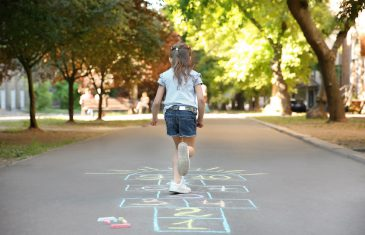 Little child playing hopscotch drawn with colorful chalk on asphalt
